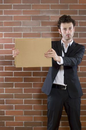 unshaved: poor young unshaved businessman standing pleading with a blank sign Stock Photo