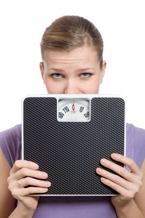 afraid young woman looking behind a weight scale over white background Stock Photo