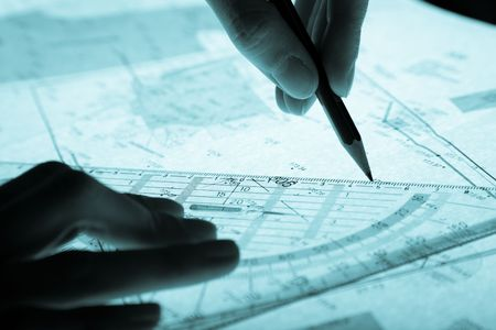 surveyors plan and hands with a pencil, monochromatic blue photo