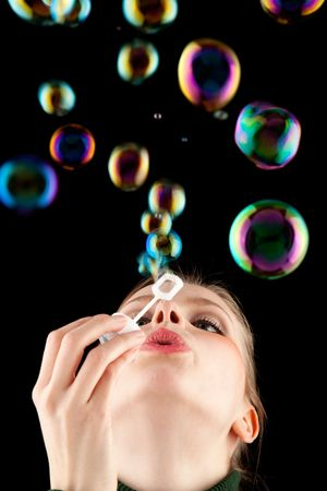 beautiful blonde girl making soap bubbles on black background photo