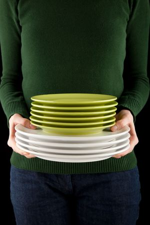 female hands holding a pile of green and white dishes