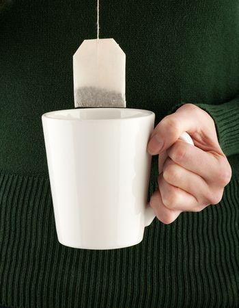 mug shot: female hands holding a teacup and teabag, studio shot