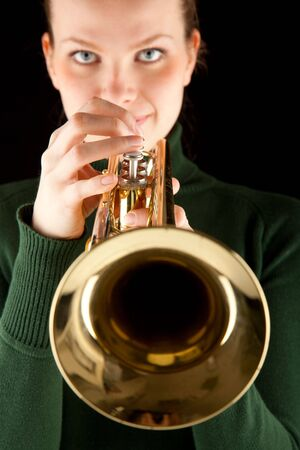 blow up: beautiful blonde girl in a green jumper holds a golden trumpet Stock Photo