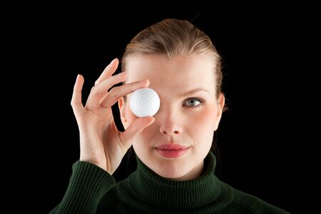 eye ball: blonde woman in a green turtleneck holds one golf ball in front of her eye