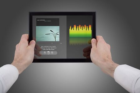 programme: male hands holding a touchpad pc, using the music programme Stock Photo