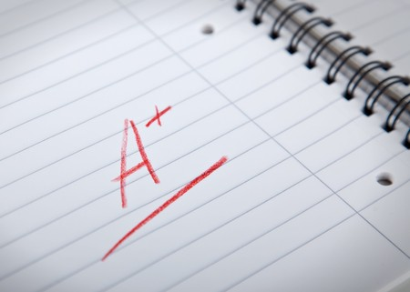 A plus grade, written in red letters in a spiral pad, shallow DOF
