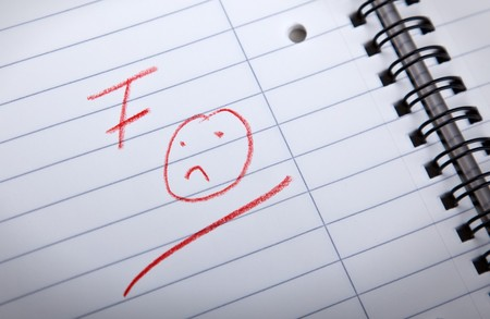 fail: F grade and a sad smilie, written in red letters in a spiral pad, shallow DOF Stock Photo