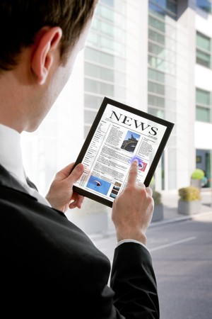 latest: Businessman holding a touchpad pc and reading a newspaper