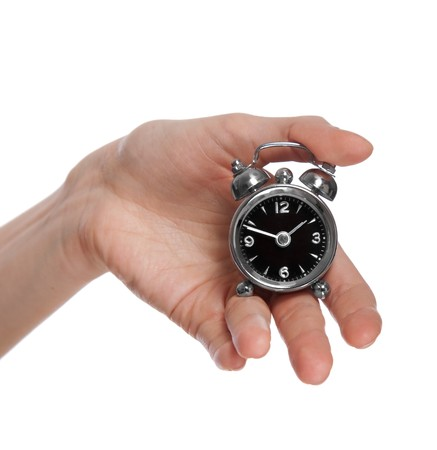 female hand holding a small alarm clock, isolated on white