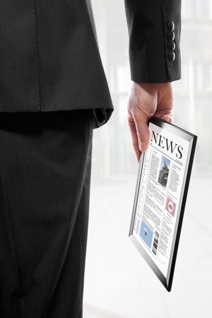 actuality: Businessman holding a touchpad pc with an electronic newspaper