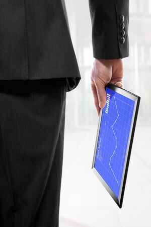 Businessman holding a touchpad pc in his hand, showing the stock market