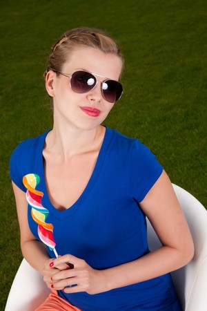 Girl with sunglasses and a lollipop sitting on a Swivel chair Stock Photo - 7952901