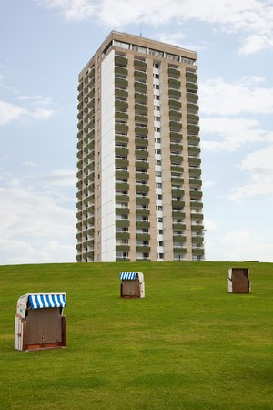 ��low income housing�: three abandoned roofed wicker beach chairs in front of an ugly tower block