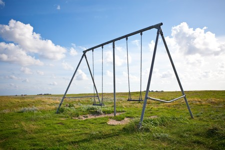 swing set: abandoned swing on a field on a sunny day