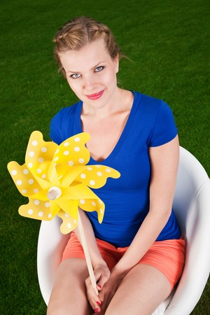 blonde girl with a pinwheel on a swivel chair Stock Photo - 7952942