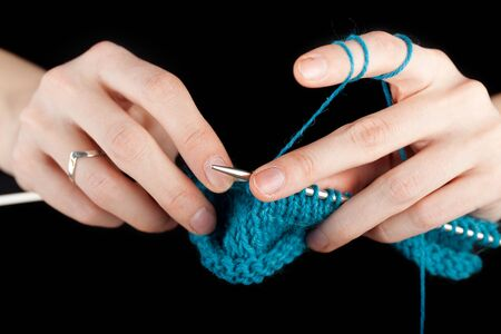Hands of a young woman knitting with blue wool