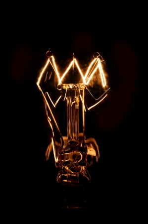 filaments: Tungsten Filament of a glowing lightbulb on a dark background