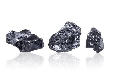 recursos naturales: tres piezas de un carbón de antracita pequeño, aislado en blanco con poca profundidad de campo