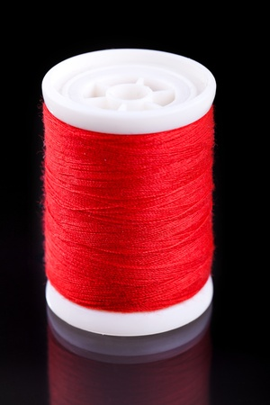 isoladed: macro shot of red bobbin thread isoladed on black background