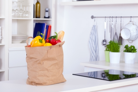 Paper shopping bag full of food on a kitchen counter Stock Photo
