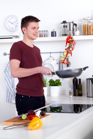 flipping: happy young man flipping chopped vegetables in the pan Stock Photo