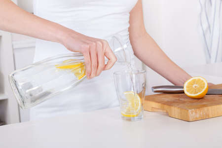 carafe: young woman preparing and drinking lemonade in her modern kitchen