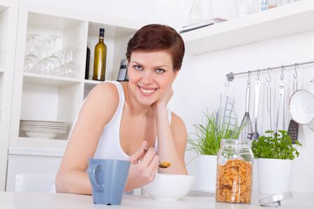cornflakes: Young attractive girl having breakfast with cornflakes and tea in her kitchen