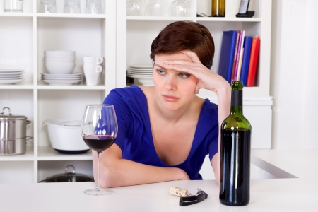 hand holding bottle: young sad thinkful woman sitting with a glass of red wine in her kitchen Stock Photo