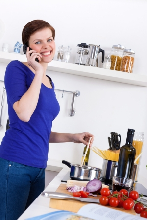 Young woman in her kitchen preparing a pasta dish and talking on the phone photo