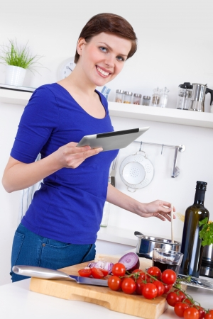 Young woman in her kitchen preparing a pasta dish and  checking the recipe on a tablet pc photo