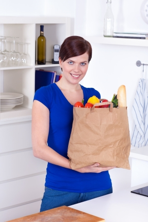 Woman with shopping bag in the kitchen at home photo