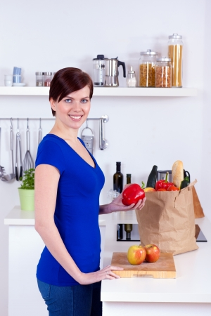 Happy woman unpacking groceries in the kitchen at home photo
