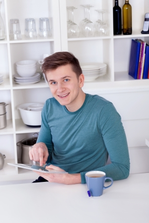 young man sitting with a tablet pc and a tea cup in the kitchen photo
