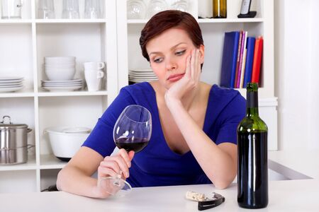 heartsickness: young sad thinkful woman sitting with a glass of red wine in her kitchen Stock Photo