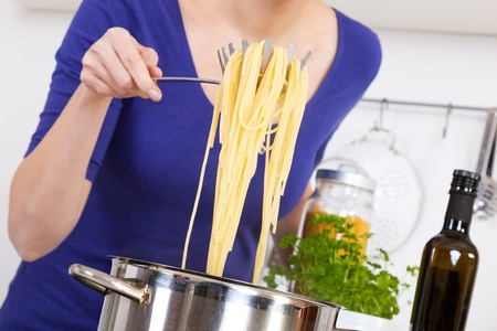 female hands raising cooked spaghettis out of the pot photo