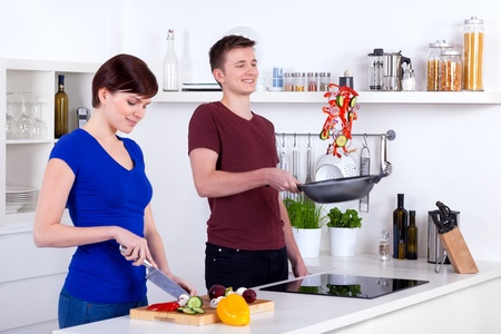 flipping: young woman chopping vegetables and man flipping food in the pan