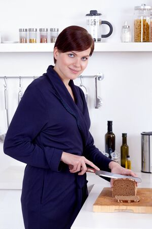 young woman cutting a slice of bread in the kitchen Stock Photo - 18387525