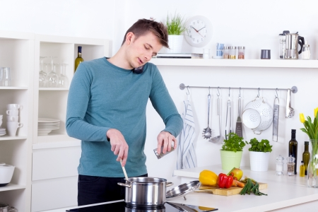 young man cooking a meal and talking on the phone in his kitchen photo