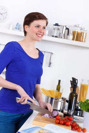 Young woman in her kitchen preparing a pasta dish photo