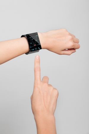 Female arm with a modern Internet Smart Watch on grey background   photo