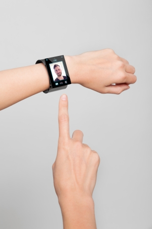 girl with a wristwatch: Female arm with a modern Internet Smart Watch on grey background On the screen you can see a videochat All Texts, Icons, Computer Interfaces of the Smart Watch where created from scratch by myself