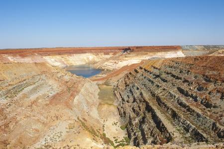 mijnbouw: Opengesneden mijnsite in West-Australië, rijk aan grondstoffen als ijzererts, goud, zilver, diamanten en nog veel meer kleurrijke, heldere blauwe lucht en veel kopie ruimte Stockfoto
