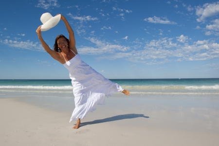 wet dress: An attractive looking mature woman in her fifties, wearing a white summer dress, is dancing and jumping at a tropical beach with a wide rimmed white hat, with ocean, horizon and blue sky as background and copy space