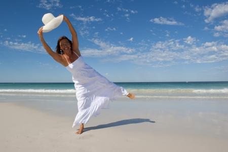 pies bailando: Una atractiva mujer de aspecto maduro de unos cincuenta años, con un vestido blanco de verano, está bailando y saltando en una playa tropical con un amplio sombrero blanco con borde, con el cielo al mar, el horizonte y el azul como fondo y el espacio de la copia