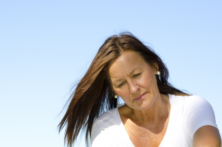 Portrait of an attractive looking middle aged woman, dressed in a white shirt, with a sad and concerned facial expression, with clear blue sky as background and copy space  photo