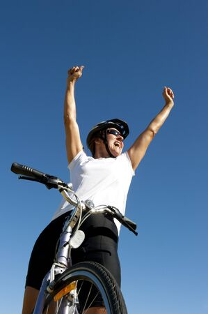 Upward view of a healthy and fit mature woman in her fifties on a bicycle, posing in a winner style, with clear blue sky and copy space  photo