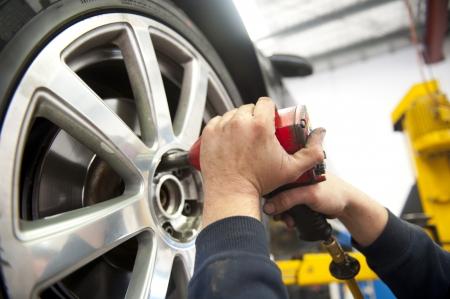 Dettaglio immagine di un meccanico cambiando un pneumatico auto in un garage, con sfondo sfocato e copia spazio