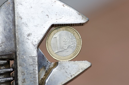 under pressure: A Euro coin crimped with pliers, as a symbol for the European currency under pressure, with blurred neutral background and copy space