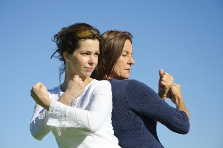 Due donne attraenti, fiducioso e determinato, in piedi schiena contro schiena, con le braccia alzate e pugni il cielo blu chiaro e copia spazio