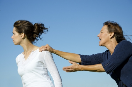 Argument between mother and daughter  Daughter is trying to get away while mother is holding her back  Clear blue sky